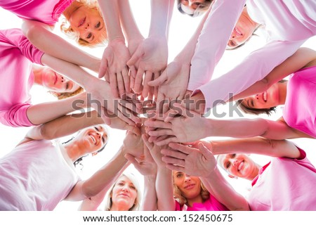 Diverse women smiling in circle wearing pink for breast cancer on white background