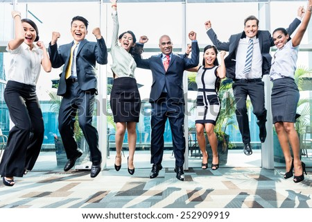Diversity business team jumping celebrating success, Chinese, Indonesian, Indian, and Caucasian ethnicities - stock photo