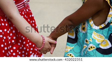 Diversity:  Caucasian and African - American little girls holding hands - stock photo