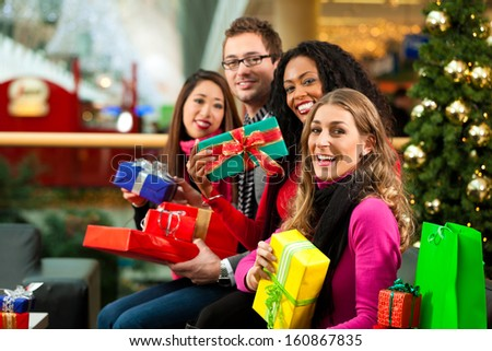 Diversity group of four people - Caucasian, black and Asian - sitting with Christmas presents and bags in a shopping mall in front of a Christmas tree with baubles - stock photo