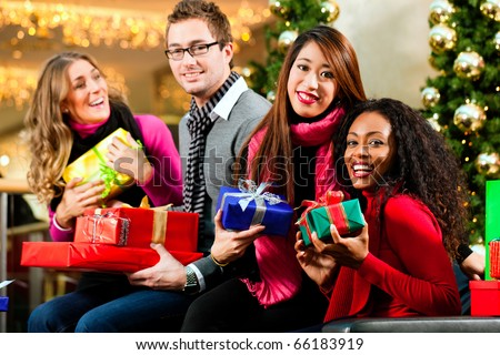 Diversity group of four people - Caucasian, black and Asian - sitting with Christmas presents and bags in a shopping mall in front of a Christmas tree with baubles