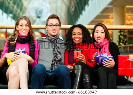 Diversity group of four people - Caucasian, black and Asian - sitting with Christmas presents and bags in a shopping mall - stock photo