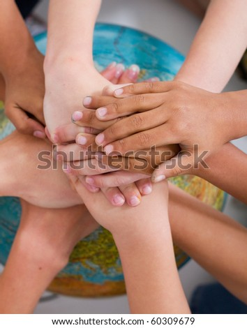 diversity kids hands together on globe - stock photo