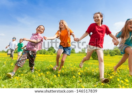 Diversity looking kids, boys and girls running in the yellow flowers spring field