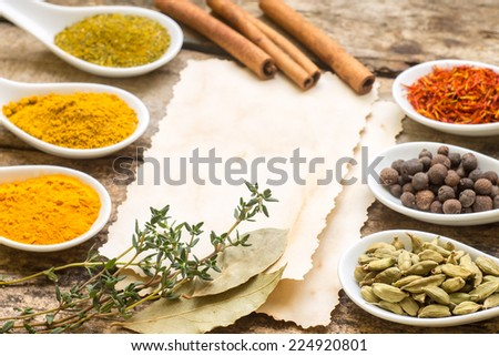 Diversity of Spices on wood background with blank paper sheet. - stock photo