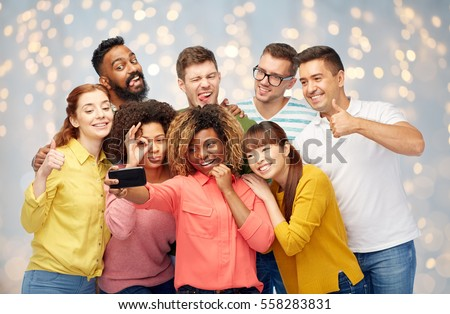 diversity, race, ethnicity, technology and people concept - international group of happy smiling men and women taking selfie by smartphone over holidays lights background