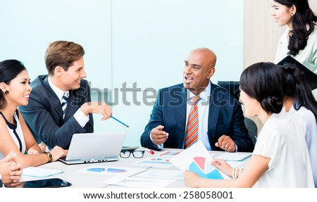Diversity team in business development meeting with charts, Indian CEO and Caucasian executive crunching numbers, charts and figures on the desk - stock photo