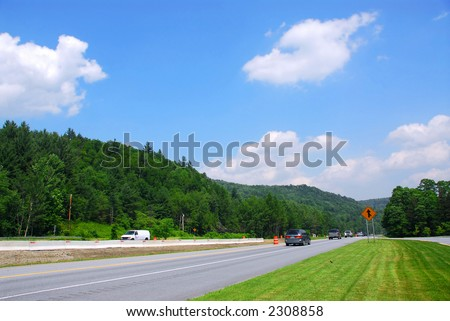 Divided highway among green hills on sunny summer day