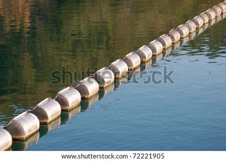 dividing line with floats on lake - stock photo