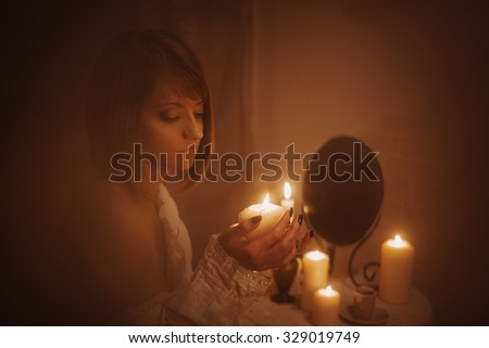 Divination woman with candle and mirror