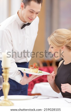 Divine dessert. Confident chef serving dessert to beautiful emotional woman having dinner in luxury restaurant  - stock photo
