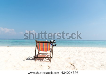 Diving mask hanging in a bright colored wooden beach chair on island tropical beach