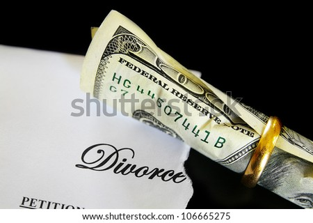Divorce decree and rolled up cash in a wedding ring - stock photo