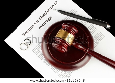 Divorce decree and wooden gavel on black background - stock photo