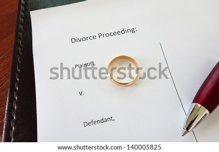 Divorce document with gold wedding ring and pen - stock photo