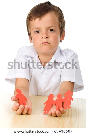 Divorce effect on kids concept with sad boy holding separated paper people family - isolated - stock photo