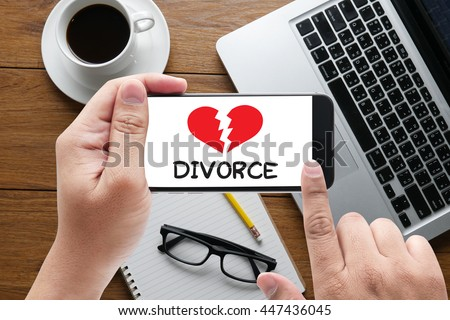 DIVORCE message on hand holding to touch a phone, top view, table computer coffee and book - stock photo
