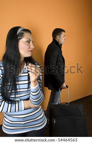 Divorce:Woman suffering , crying  and hold her wedding ring ,looking away  while the man leaves house with baggage - stock photo