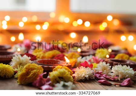 Diwali Candles and Oil Lamps with flowers on a wooden background  - stock photo