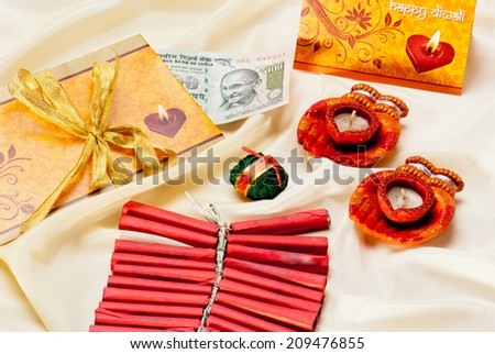 Diwali Greeting Card with firecrackers and hundred-rupee currency on silk background during Diwali festival India Asia South East Asia - stock photo