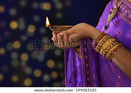 Diwali or festive of lights. Traditional Indian festival, woman in sari hands holding oil lamp, with defocus light background. - stock photo