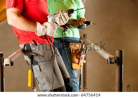 DIY couple in home improvement with hand drill standing on a scaffold - stock photo