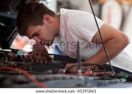 DIY mechanic looking under hood. - stock photo