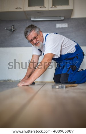 DIY, repair, building and home concept - close up of male hands lying parquet floor board/laminate flooring (shallow DOF; color toned image) - stock photo