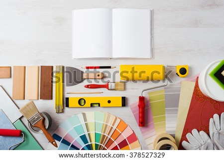 DIY training open manual with work tools, color swatches and painting rollers at bottom, top view - stock photo