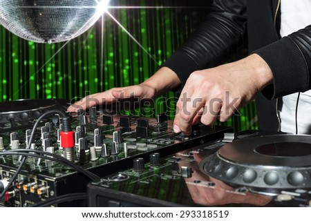 DJ at dance party mixes track on sound mixer, nightclub with striped green interior and silver disco ball with star, professional stereo electronic equipment  - stock photo