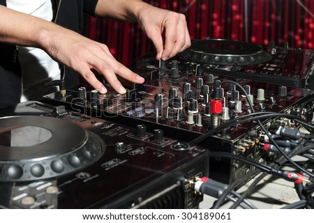 DJ at dance party mixes track on sound mixer, nightclub with striped red interior, professional stereo electronic equipment - stock photo