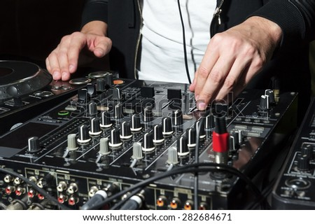 DJ at nightclub party mixes track on sound mixer, professional stereo electronic equipment, selective focus  - stock photo