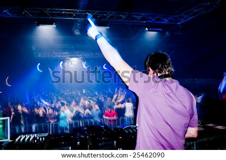 Dj at the concert, blurred crowd on background - stock photo