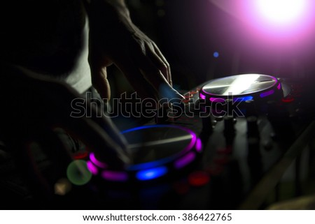 DJ console mixer controlling with two hand in nightclub. - stock photo