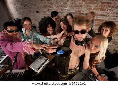 DJ crowded by fans and requests at a party - stock photo