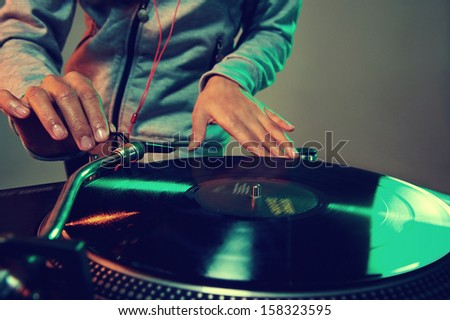 Dj hands on equipment deck and mixer with vinyl record at party - stock photo