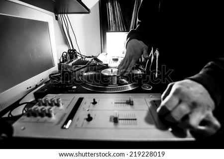 Dj in studio uses turntable and mixer for scratching. Black and white image  - stock photo