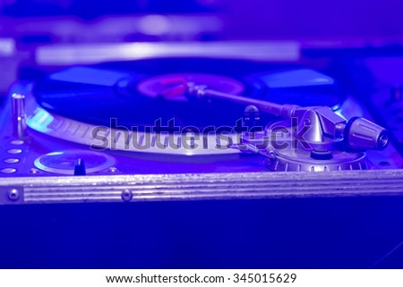Dj mixer at nightclub. In the background led light show - stock photo