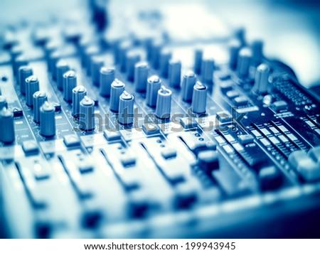 DJ mixer desk in blue tone. Tilt-shift lens use. - stock photo