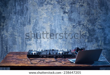 Dj mixer with headphones and laptop on wooden table close-up. - stock photo