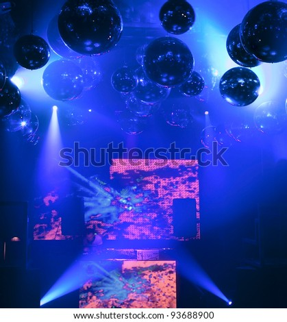 DJ mixes at a nightclub on the scene for a game. Bright beautiful lighting