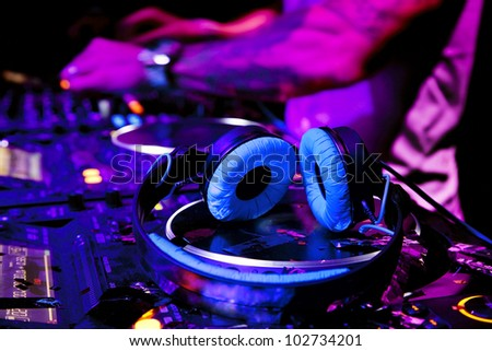 Dj mixes the track in nightclub at party. DJ headphones - stock photo