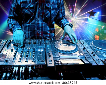 Dj mixes the track in the nightclub at a party. In the background laser light show - stock photo