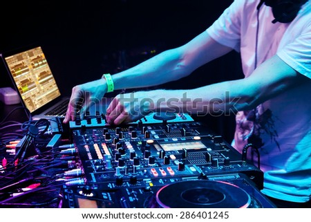 Dj mixes the track in the nightclub at party. Headphones in foreground and DJ hands in motion - stock photo