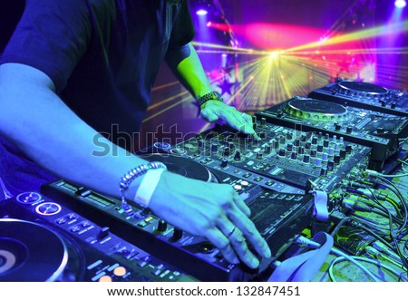 Dj mixes the track in the nightclub at party. In the background laser light show - stock photo