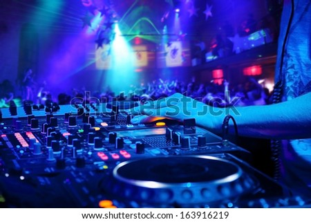 Dj mixes the track in the nightclub at party.  On background of people dancing and a laser show - stock photo