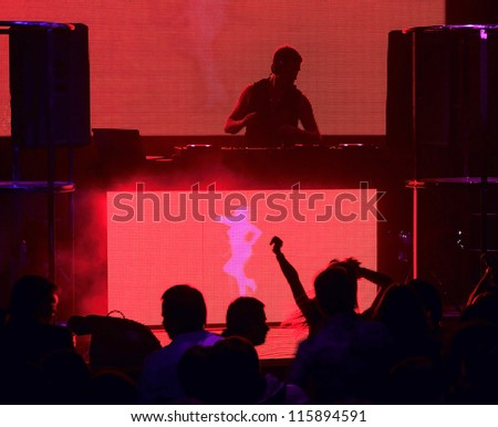 Dj mixes the track in the nightclub at party. Silhouettes of dancing people - stock photo