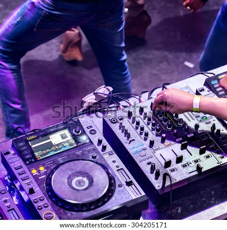 Dj mixes the track in the nightclub at party. Silhouettes of dancing people in motion. Top view - stock photo