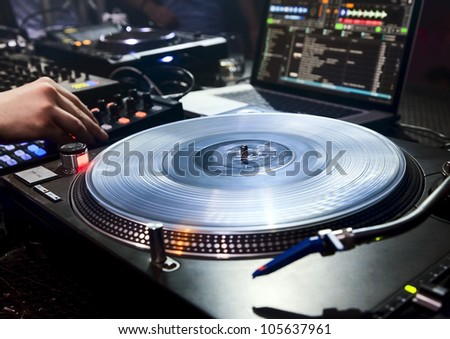 Dj mixes the track in the nightclub at party. Vinyl Player in foreground - stock photo