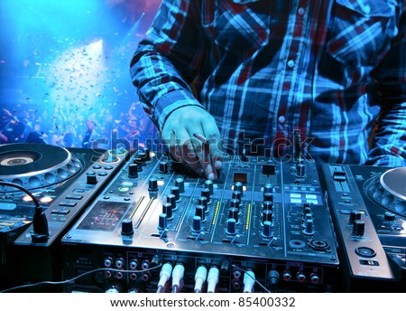 Dj mixes the track with a cigarette in his hand in the nightclub at a party. In the background people dancing and having fun
